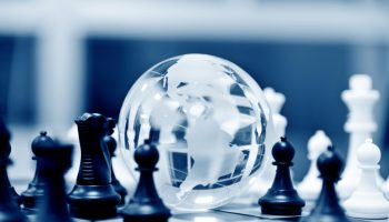 Crystal globe and chess pieces on chessboard